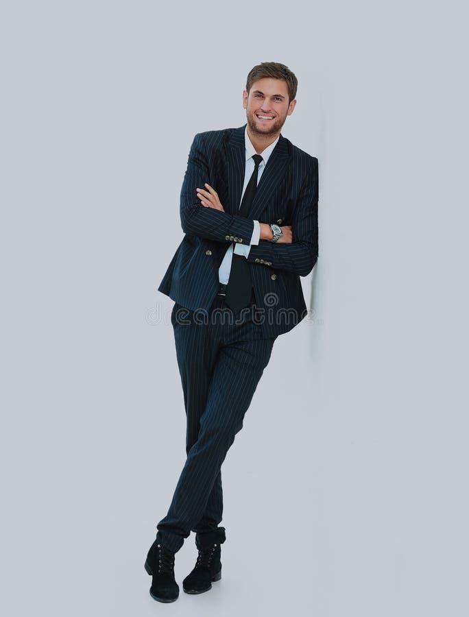 Retrato de un hombre joven hermoso en un juego de asunto Colocación cerca de la pared foto de archivo
