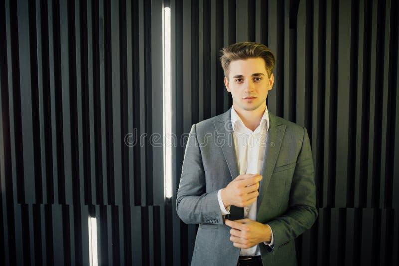 Retrato de un hombre joven hermoso en un traje de negocios contra la pared oscura de madera en oficina moderna imagenes de archivo