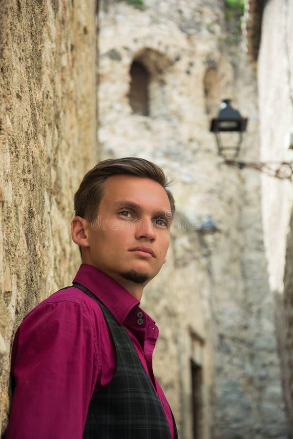 Retrato de un hombre joven hermoso en una calle medieval en Girona, foto de archivo