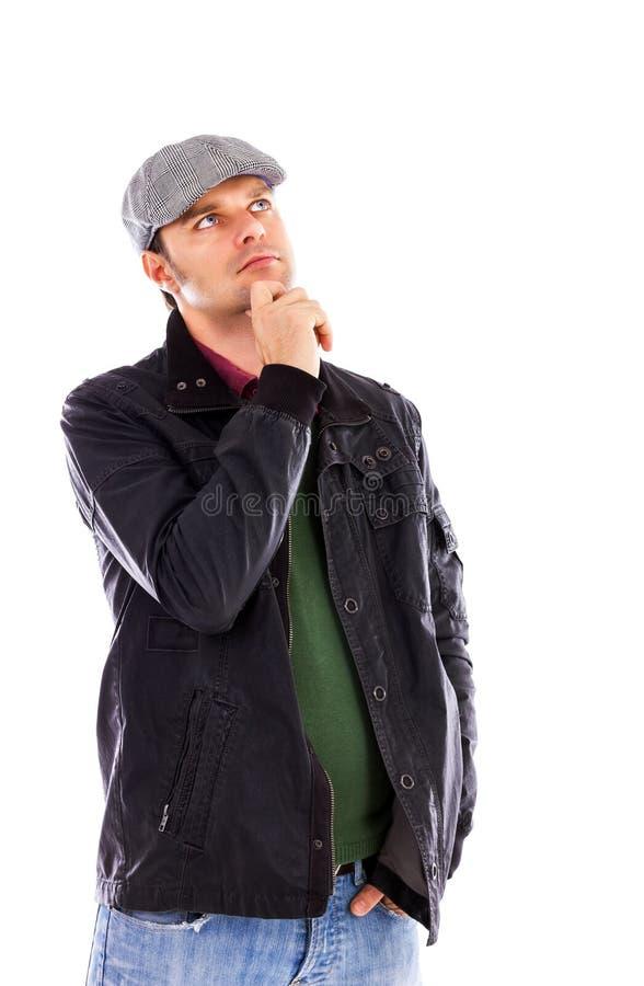 Retrato de un hombre joven pensativo con la mano en la barbilla que mira para arriba imagen de archivo