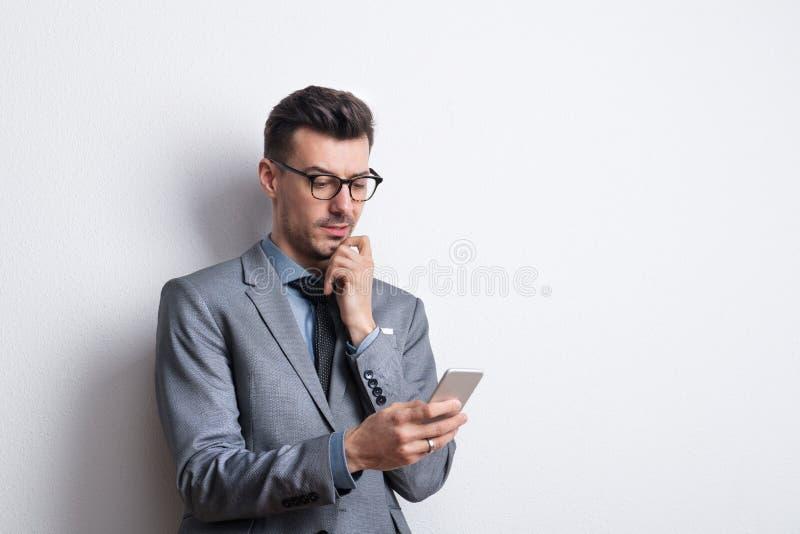 Retrato de un hombre joven pensativo con una pluma y de un diario en un estudio, planeando imagen de archivo
