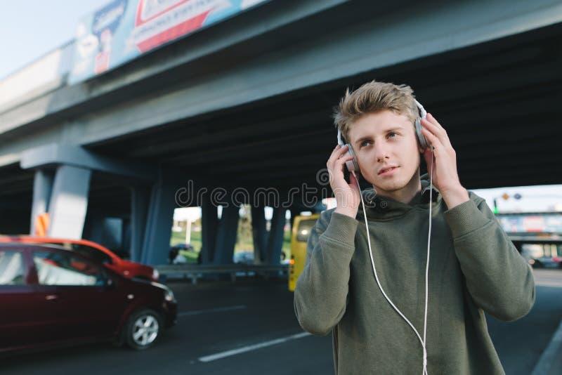 Retrato de un hombre joven que camina en la ciudad en el fondo de la arquitectura urbana y que escucha la música en auriculares E fotos de archivo libres de regalías