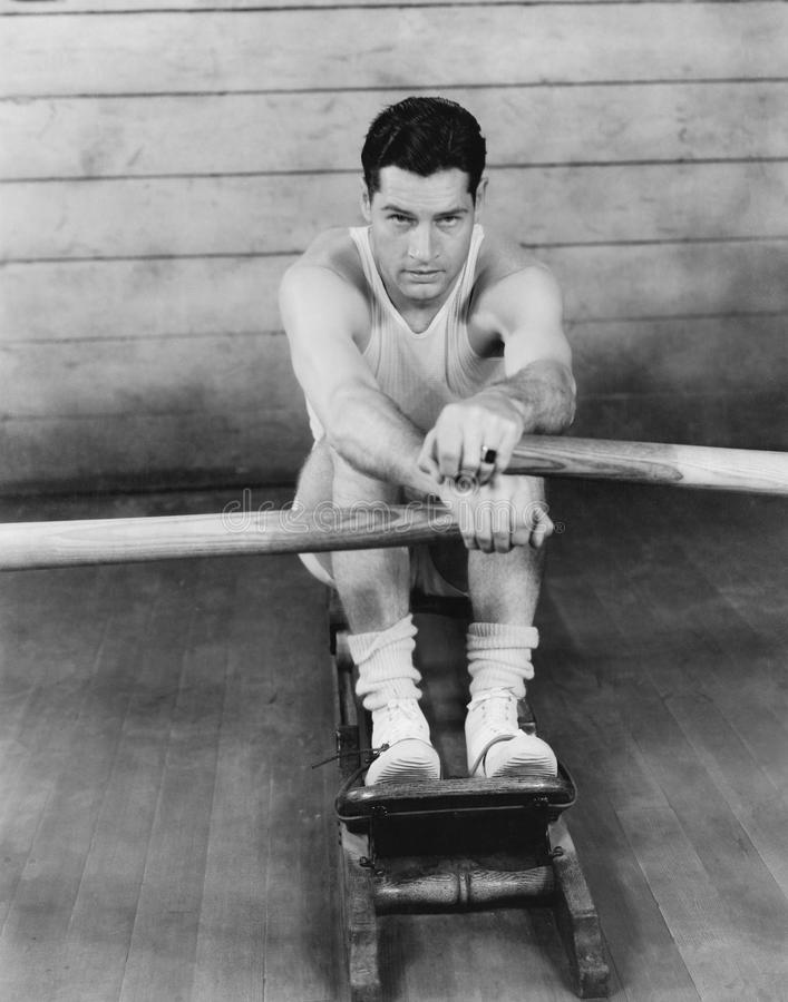 Retrato de un hombre joven que ejercita en un aparato de remar (todas las personas representadas no son vivas más largo y ningún  fotos de archivo
