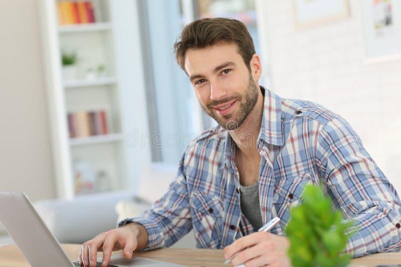 Retrato de un hombre joven que trabaja en casa en su ordenador portátil imagen de archivo libre de regalías