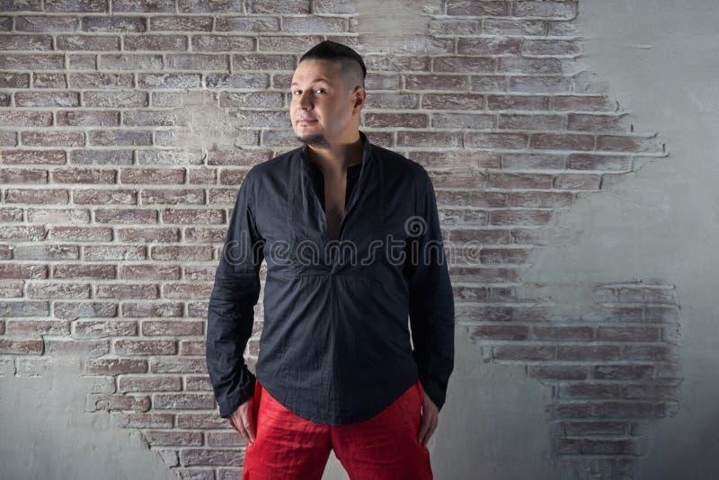 Retrato de un hombre joven, rechoncho, vestido en holguras rojas y una camisa negra fotos de archivo
