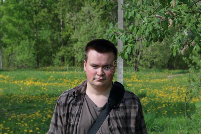 Retrato de un hombre joven regordete En un prado de la primavera con la hierba y los árboles jovenes verdes claros imagenes de archivo