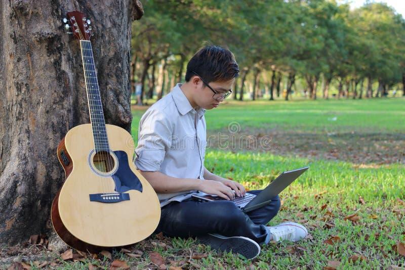 Retrato de un hombre joven relajado que mecanografía en un ordenador portátil en parque al aire libre de la naturaleza fotografía de archivo