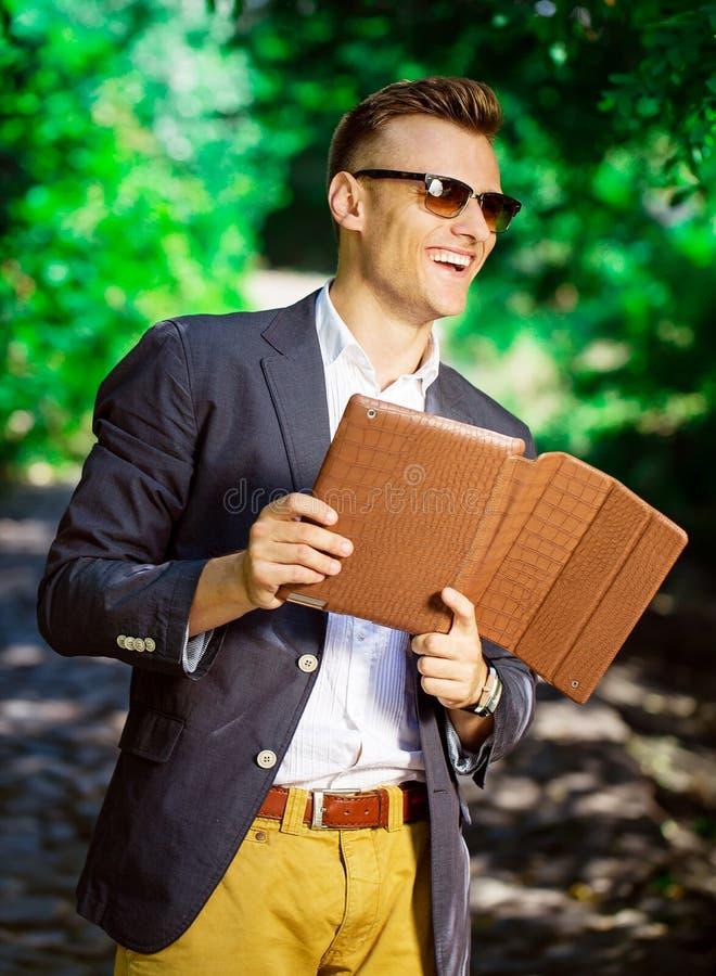 Retrato de un hombre joven sonriente en los vidrios que se colocan en el parque imagen de archivo