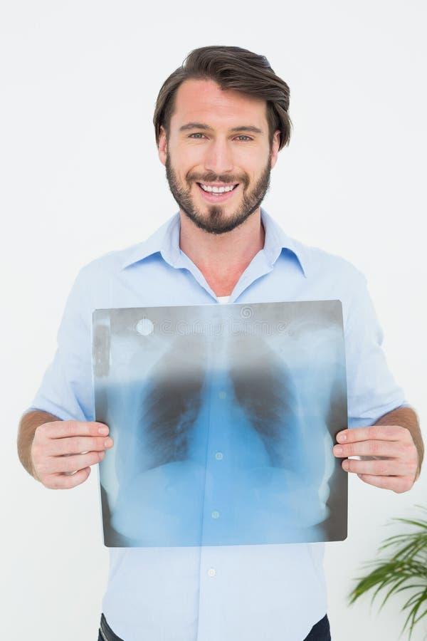 Retrato de un hombre joven sonriente que lleva a cabo la radiografía del pulmón foto de archivo libre de regalías