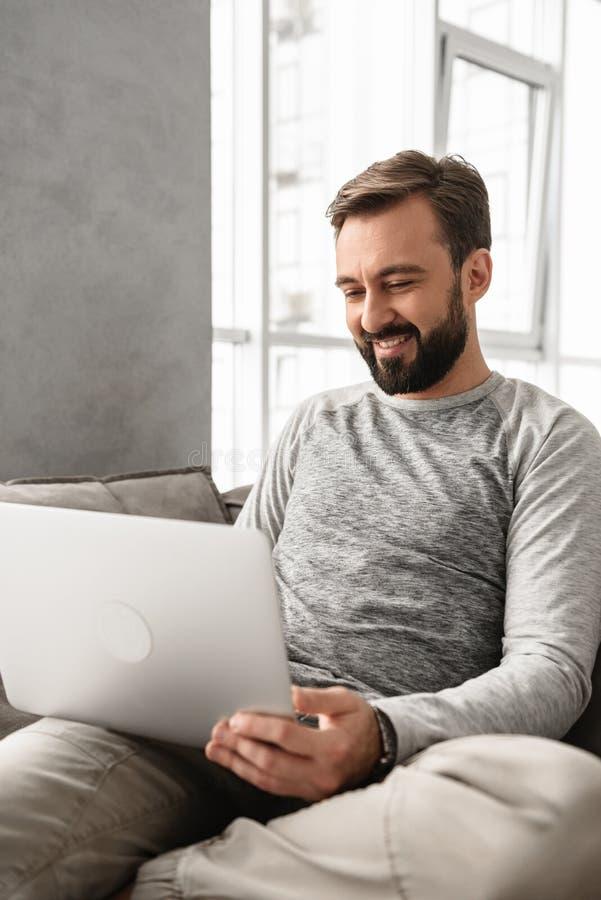 Retrato de un hombre joven sonriente que trabaja en el ordenador portátil fotografía de archivo libre de regalías