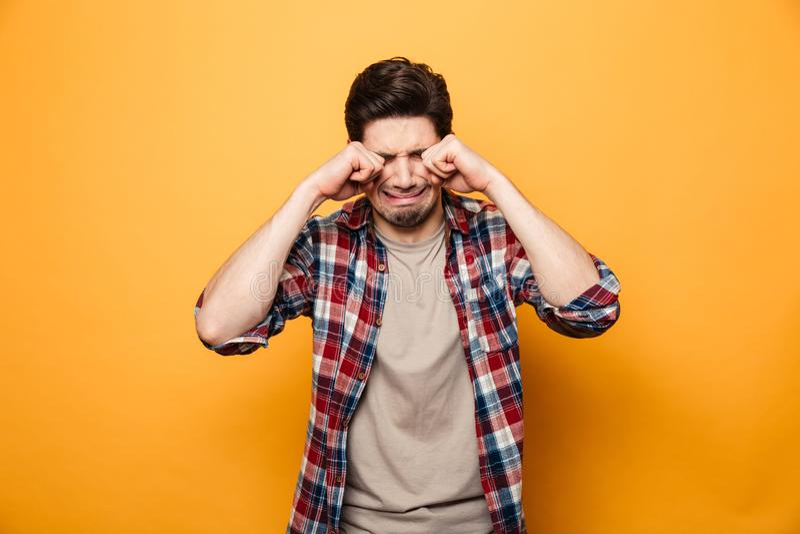 Retrato de un hombre joven triste que llora ruidosamente fotografía de archivo