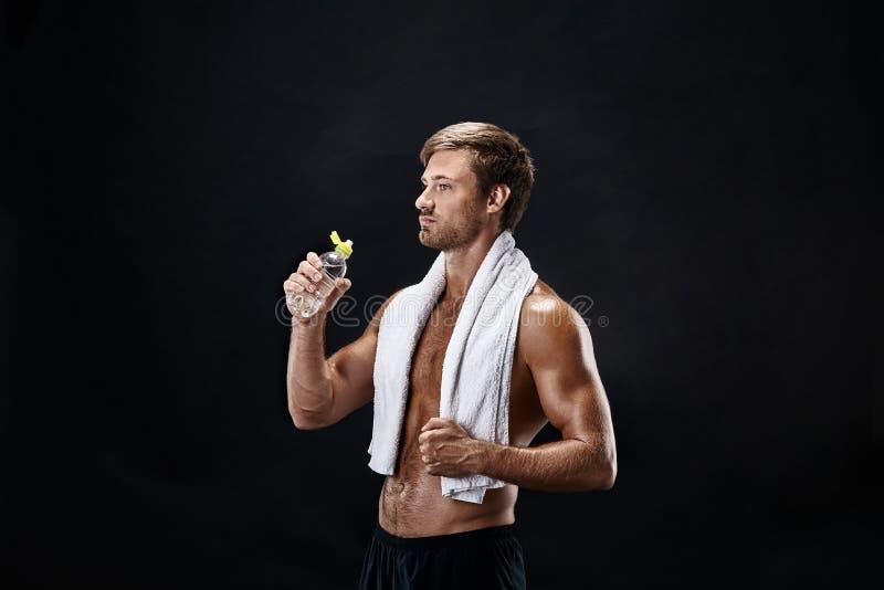 Retrato de un hombre de la aptitud con la toalla en los hombros que miran lejos Hombre joven feliz que se relaja después de entre imagen de archivo