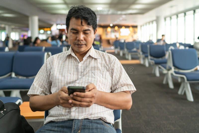Retrato de un hombre de la Edad Media que se sienta en banco y utilizar el teléfono elegante, sonrisa con mirada en el teléfono c imagen de archivo
