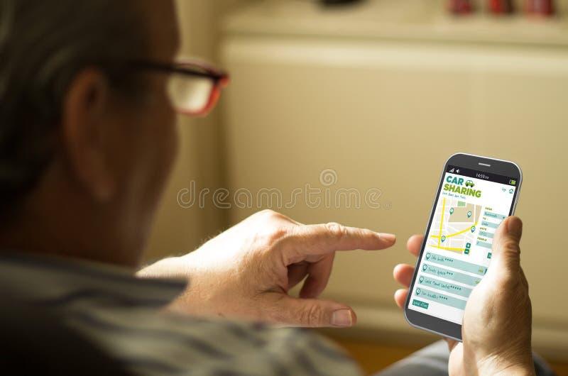Retrato de un hombre maduro con la distribución de coche app en un teléfono móvil imagen de archivo