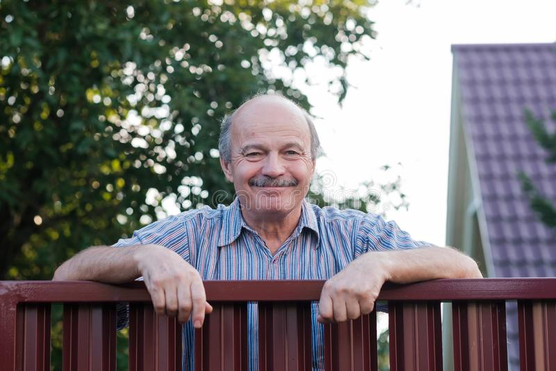 Retrato de un hombre maduro hermoso feliz que se coloca que se inclina en la cerca roja del metal fotos de archivo libres de regalías