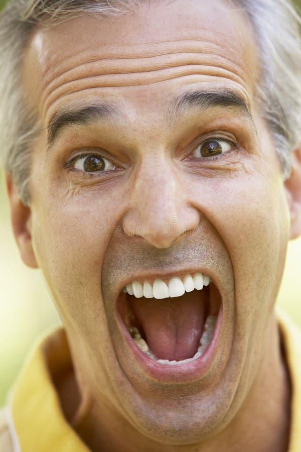 Retrato de un hombre mayor con su boca abierta foto de archivo