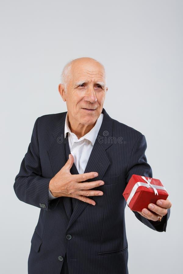 Retrato de un hombre mayor en un fondo blanco, en el estudio, en un traje elegante con una caja de regalo roja en su mano imagenes de archivo
