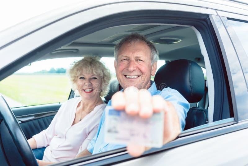 Retrato de un hombre mayor feliz que muestra su carné de conducir mientras que fotografía de archivo