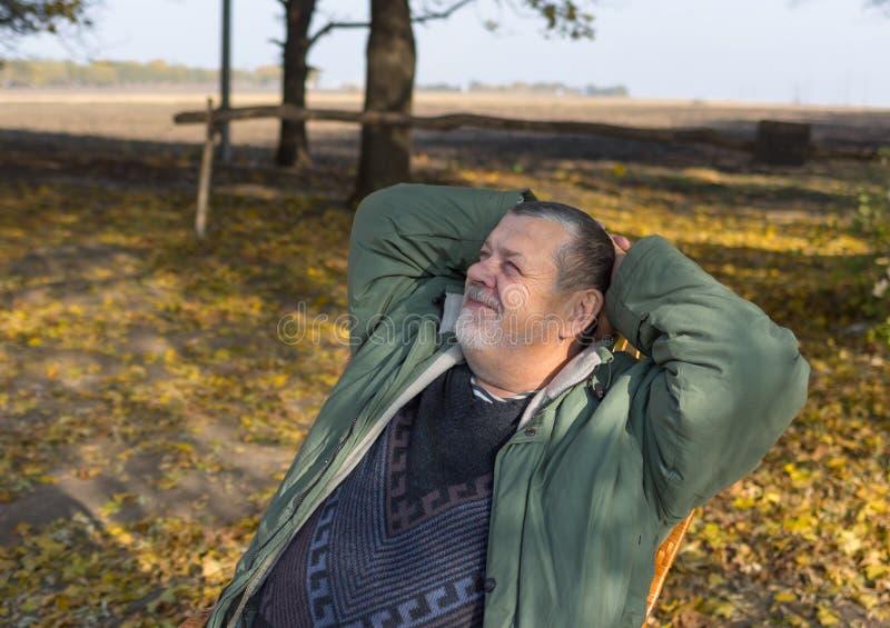 Retrato de un hombre mayor que se relaja en silla de mimbre en el día otoñal caliente y soleado fotografía de archivo libre de regalías