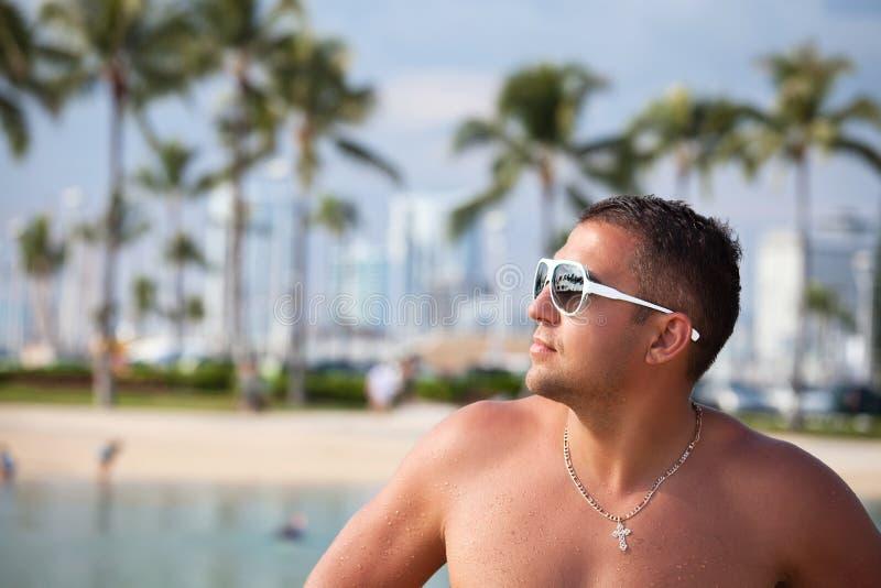 Retrato de un hombre muscular atractivo mojado joven que se coloca en la playa foto de archivo