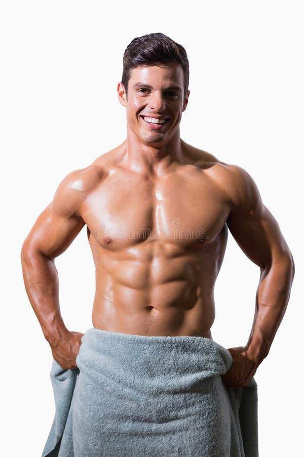 Retrato de un hombre muscular descamisado sonriente envuelto en toalla imagen de archivo libre de regalías