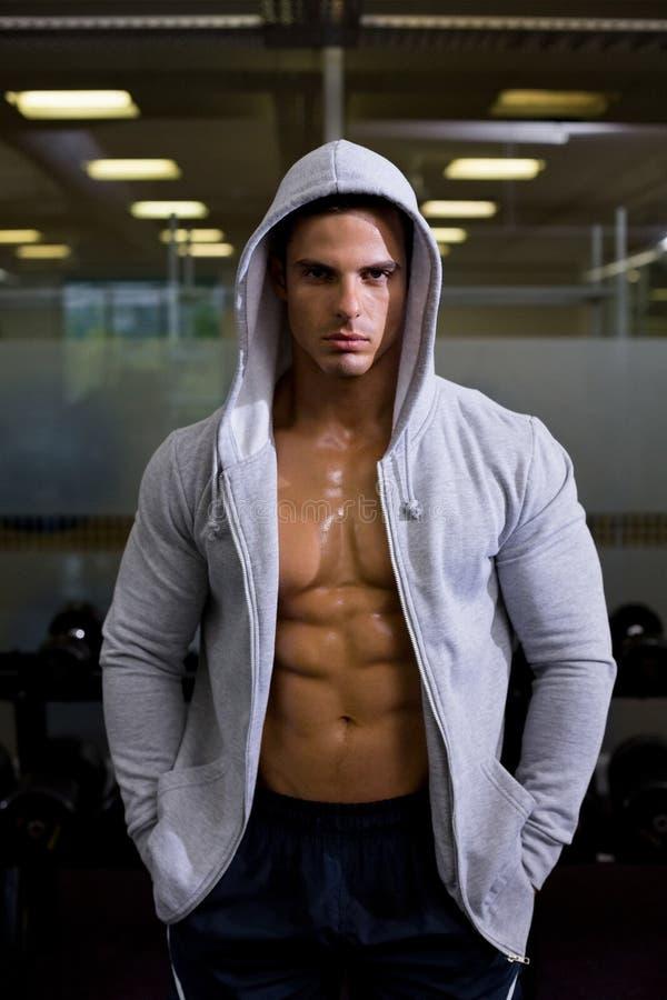 Retrato de un hombre muscular en chaqueta de la capilla en el gimnasio foto de archivo libre de regalías