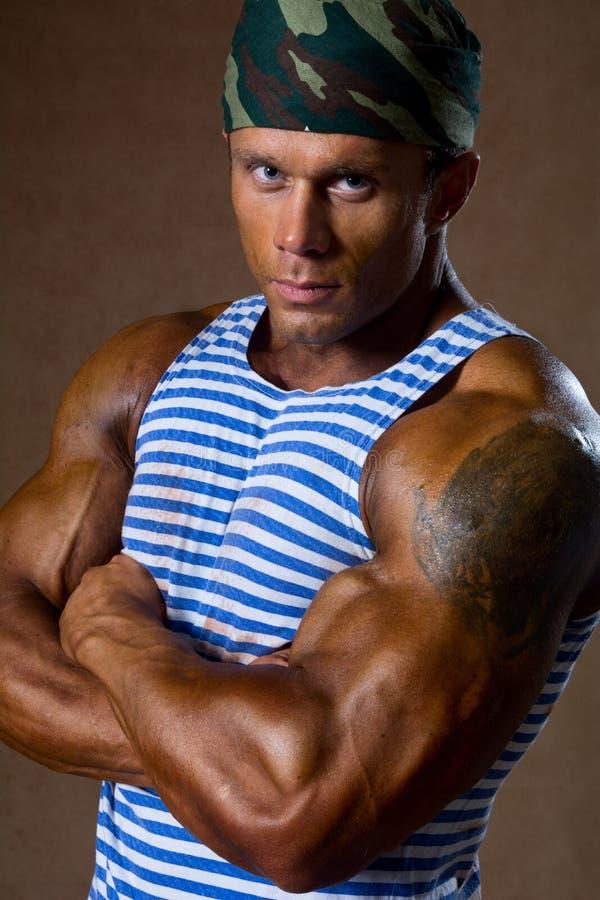 Retrato de un hombre muscular fuerte en una camisa rayada. imagen de archivo