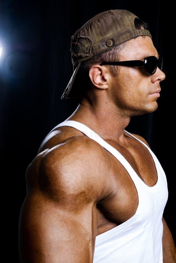 Retrato de un hombre muscular hermoso que lleva un casquillo que se coloca en la banda imagen de archivo