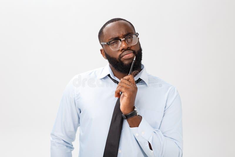 Retrato de un hombre de negocios afroamericano pensativo en un traje gris que piensa con la pluma en su mano foto de archivo libre de regalías
