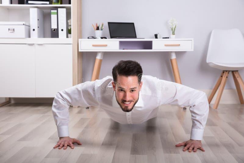 Retrato de un hombre de negocios Doing Push Up en piso foto de archivo
