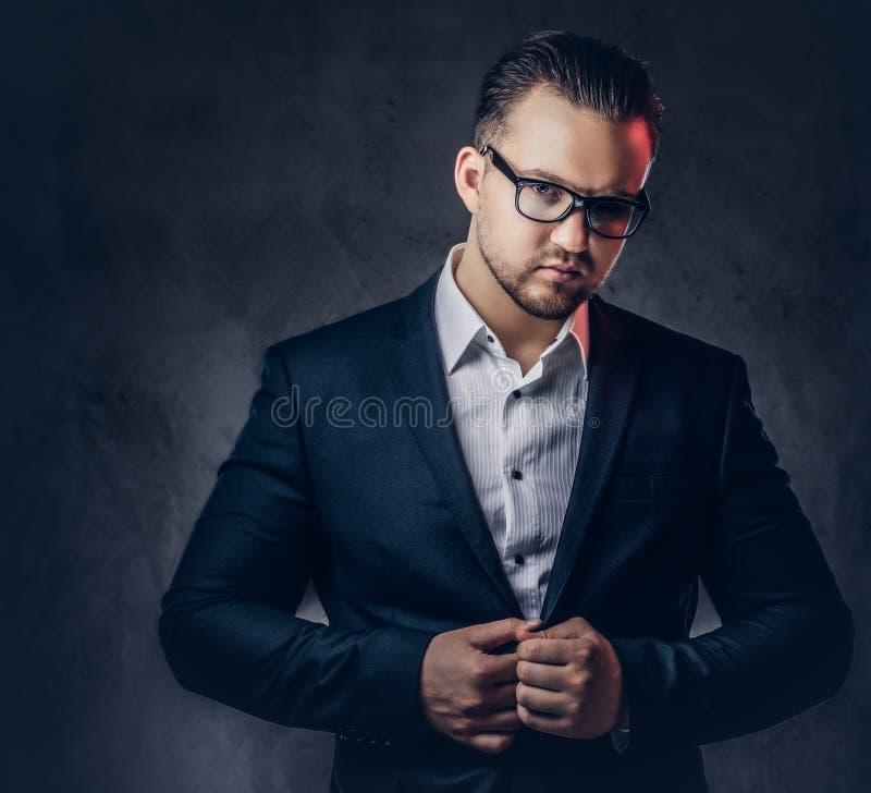 Retrato de un hombre de negocios elegante con la cara seria en un traje formal elegante y vidrios foto de archivo libre de regalías
