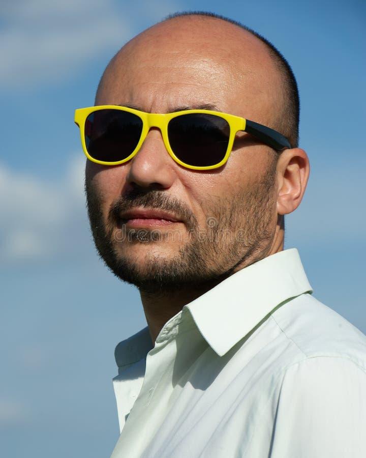 Retrato de un hombre de negocios en gafas de sol modernas contra SK azul foto de archivo