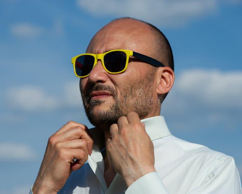Retrato de un hombre de negocios en gafas de sol modernas contra SK azul imagenes de archivo