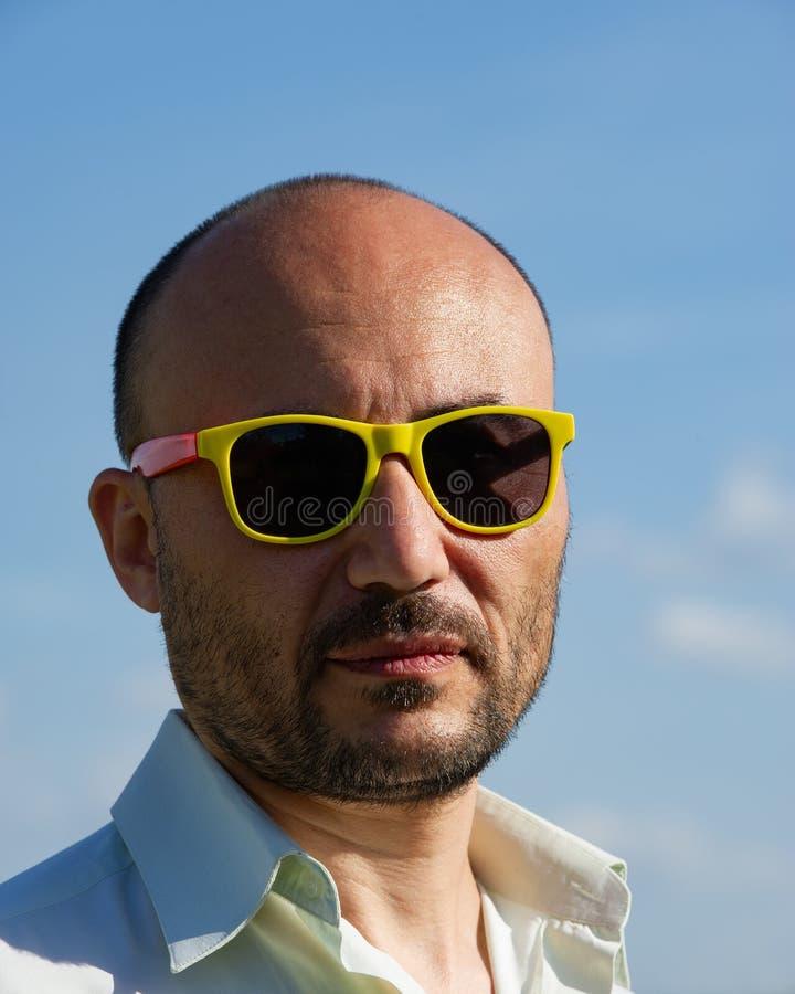Retrato de un hombre de negocios en gafas de sol modernas contra SK azul imagen de archivo
