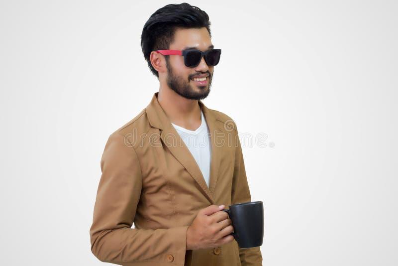 Retrato de un hombre de negocios joven asiático hermoso que sostiene la taza de co foto de archivo