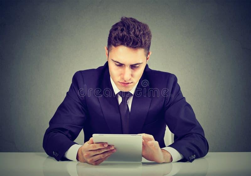 Retrato de un hombre de negocios joven que usa una PC de la tableta que se sienta en la tabla fotos de archivo libres de regalías