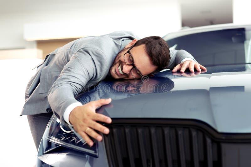 Retrato de un hombre de negocios que sonríe alegre y que abraza un nuevo coche en la sala de exposición de la representación imagen de archivo