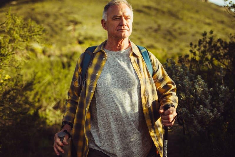 Retrato de un hombre que camina en una colina foto de archivo