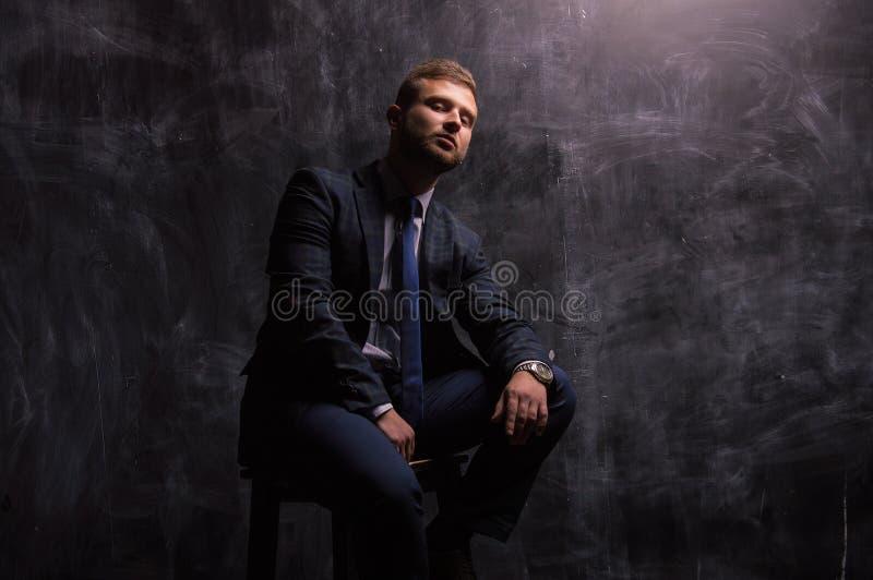 Retrato de un hombre que se sienta en una silla fotos de archivo