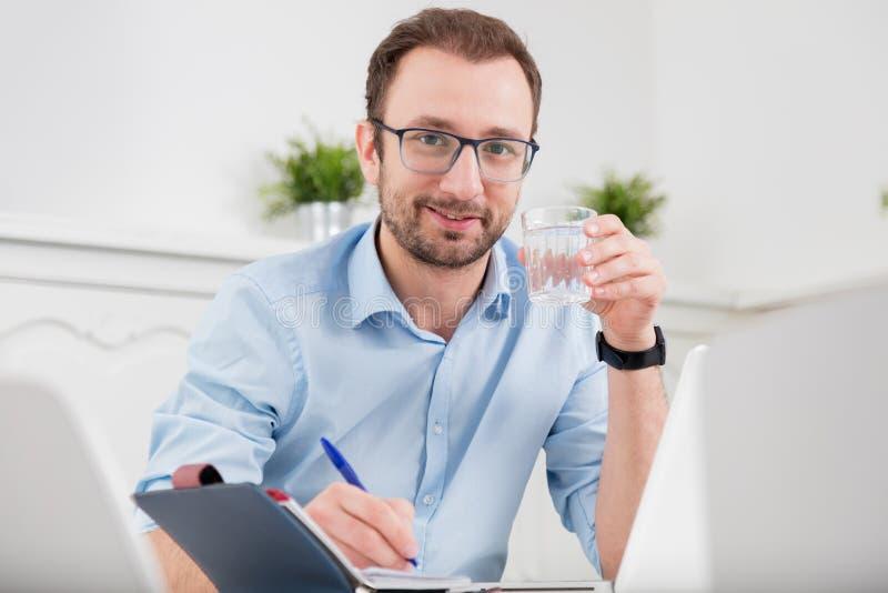 Retrato de un hombre que sostiene el vidrio de agua en el escritorio en el offi fotografía de archivo