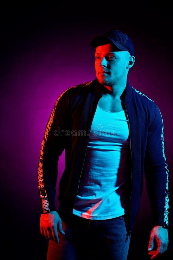 Retrato de un hombre serio feliz joven en el estudio Modelo masculino de la alta moda en las luces de neón brillantes coloridas q foto de archivo