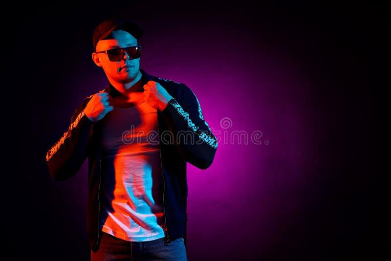 Retrato de un hombre serio feliz joven en el estudio Modelo masculino de la alta moda en las luces de neón brillantes coloridas q fotos de archivo