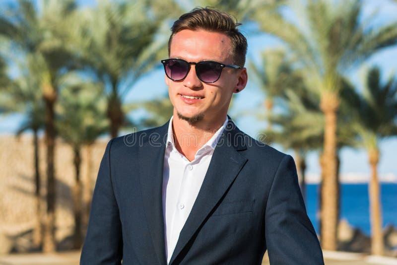 Retrato de un hombre sonriente hermoso joven en un traje en el fondo y las palmeras del mar foto de archivo libre de regalías