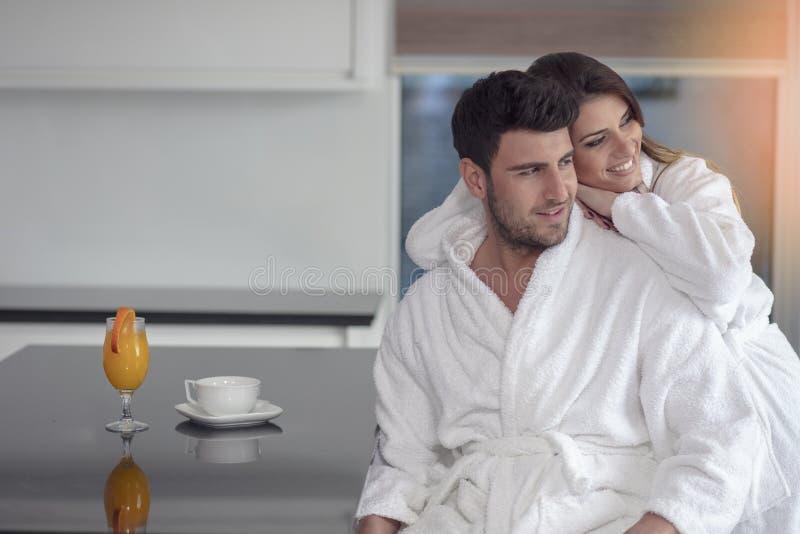 Retrato de un hombre y de su esposa en la cocina mientras que desayunando imagenes de archivo