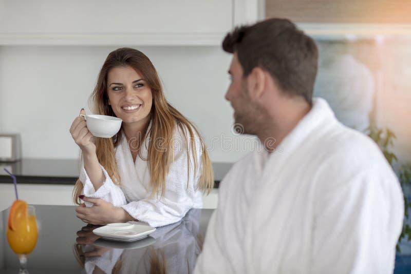 Retrato de un hombre y de su esposa en la cocina mientras que desayunando imagen de archivo libre de regalías
