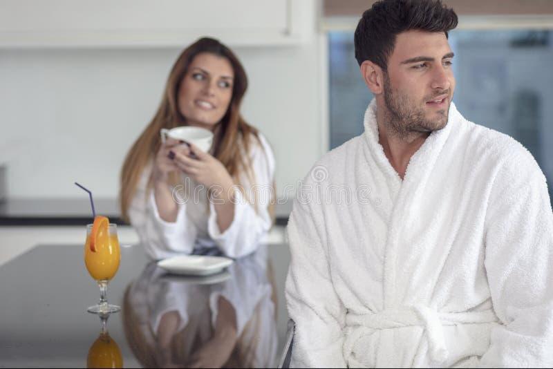 Retrato de un hombre y de su esposa en la cocina mientras que desayunando foto de archivo