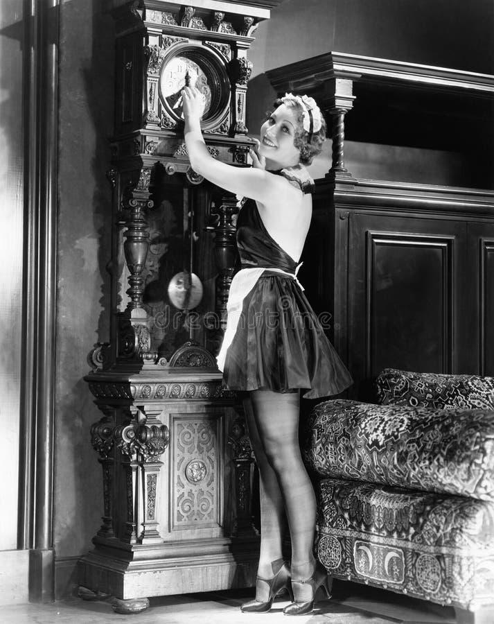 Retrato de un housekeeeper joven que ajusta tiempo en un reloj (todas las personas representadas no son vivas más largo y ningún  fotografía de archivo libre de regalías