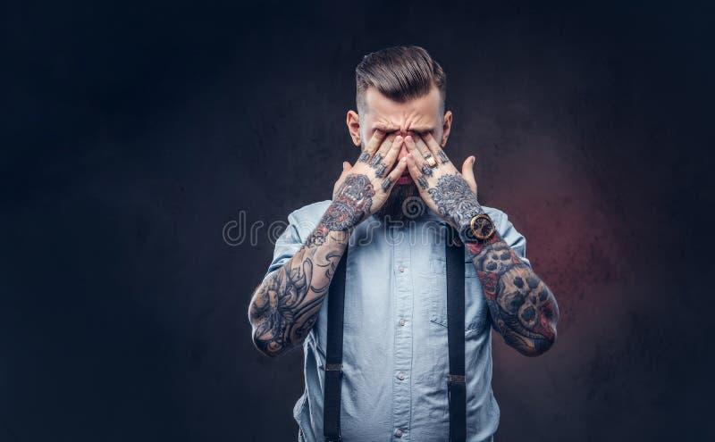 Retrato de un inconformista pasado de moda apenado en una camisa azul y ligas imágenes de archivo libres de regalías
