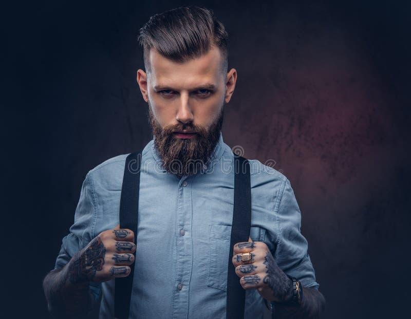 Retrato de un inconformista pasado de moda hermoso en una camisa azul y ligas fotografía de archivo