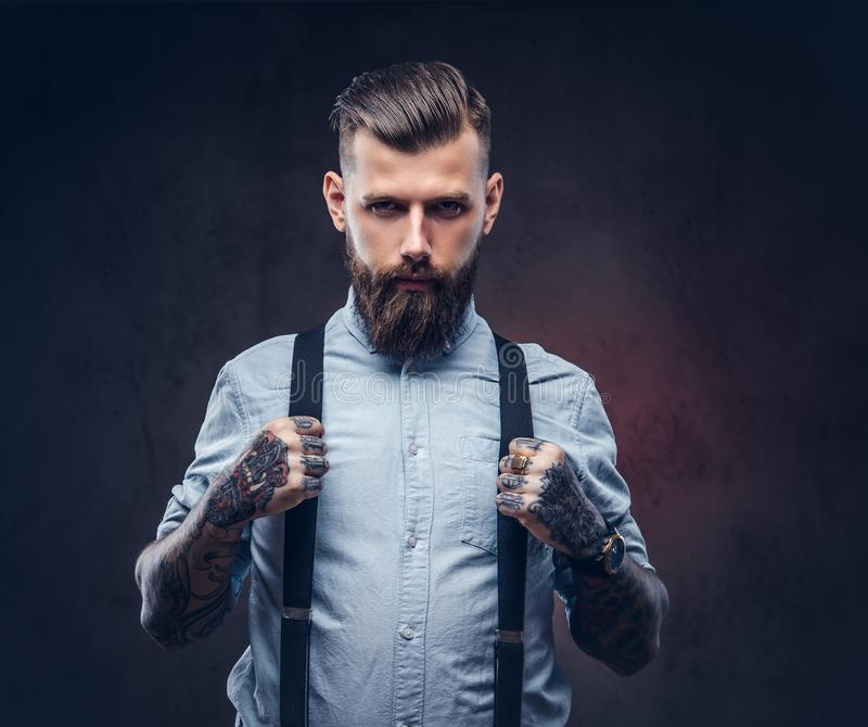 Retrato de un inconformista pasado de moda hermoso en una camisa azul y ligas imagenes de archivo